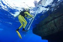 Scuba diver and boat. Scuba diver climb the ladder of the dive boat stock photo