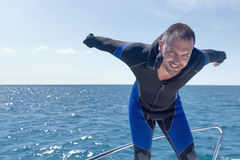 Scuba diver on boat, putting on his wetsuit. Royalty Free Stock Photos
