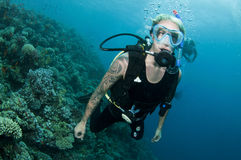 Scuba diver and coral reef. Young male scuba diver underwater with coral reef in background Royalty Free Stock Photos