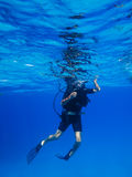 Scuba diver descends in blue water Royalty Free Stock Photos