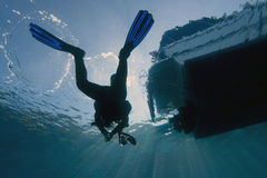 Scuba diver & dive boat. A female scuba diver is ascending from underwater towards a dive boat royalty free stock photo