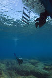Scuba diver & dive boat. A female scuba diver below a dive boat royalty free stock images