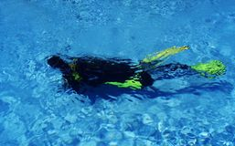 Scuba Diver Diving In Pool. Diver exercising with equipment in turquise water. Diver is visible through surface Royalty Free Stock Photo