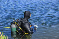 Scuba diver entering lake. Scuba diver with full face mask entering lake Royalty Free Stock Photography