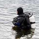 Scuba diver enters the mountain lake water. practicing techniques for emergency rescuers. immersion in cold water.  stock photo