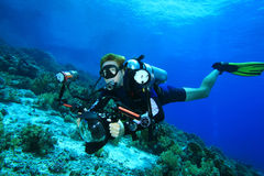 Scuba Diver explores coral reef with his camera Royalty Free Stock Photo
