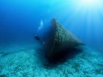 A Scuba diver explores a sunken shipwreck in the mediterranean sea stock photos