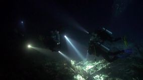 Scuba diver with flashlight on background of bottom at night underwater. Amazing unique beautiful video. Relax stock video footage