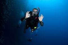 Scuba diver gesturing OK. Middle aged scuba diver gesturing ok sign with hands, blue water in background. Photograph taken in Blue Hole, Dahab, Egypt royalty free stock image