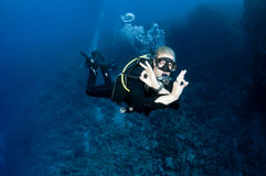 Scuba diver gives OK sign. Male scuba diver swims in clear blue water and makes the OK sign Stock Photos
