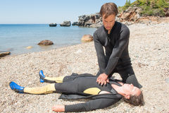 Diver rescue. Scuba diver giving CPR to a casualty Royalty Free Stock Photo
