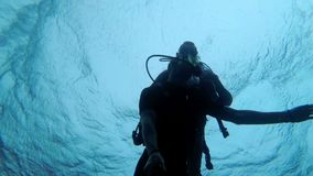 Scuba diver with instructor diving in the Red Sea, Egypt. Diving in a scuba diver suit in clear water. Underwater shooting on the selfie stick. Silhouettes of stock video