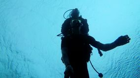Scuba diver with instructor diving in the Red Sea, Egypt. Diving in a scuba diver suit in clear water. Underwater shooting on the selfie stick. Silhouettes of stock video footage