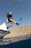 Scuba diver jumps off boat. Giant sride of a boat into the ocean royalty free stock photo