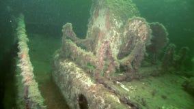 Scuba diver near rusty wreckage shipwreck on beach of White Sea Russia.