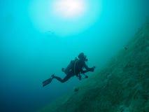 Scuba diver passing as bubble rising. Undersea Scuba diver as bubble rising royalty free stock photo