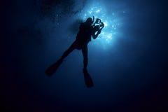 Scuba Diver Silhouette with Video Cam. Scuba Diver dives down into the deep Stock Photography