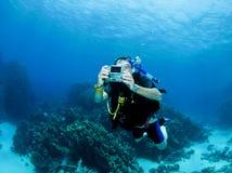 Scuba diver with small camera. Male scuba diver swimms with camera Stock Photos