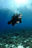 Scuba diver on the surface. Male scuba diver on surface with mountains behind Stock Photography
