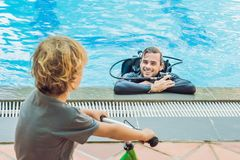 Scuba diver in swimming pool and boy royalty free stock photo