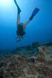 Scuba Diver Underwater. A female scuba diver is swimming underwater above an an rocky reef. dep blue water background with sunbeams royalty free stock photo