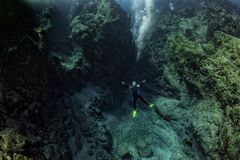 Scuba diver underwater in the deep blye ocean abyss royalty free stock photography