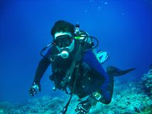 Scuba diver is underwater. He is wearing in full scuba-diving equipment: mask, regulator, BCD, fins. Diver is on the blue water ba. Scuba diver is underwater. He royalty free stock photos