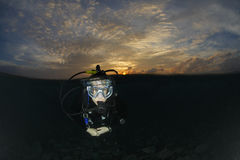 Scuba Diver in water before a sunrise dive Stock Photos
