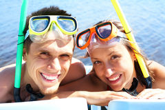 Scuba divers. Portrait of cheerful couple in aqualungs looking at camera with smiles Royalty Free Stock Images