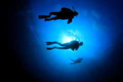 Scuba Divers. In blue ocean, silhouette against sun royalty free stock images