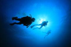 Scuba Divers. In blue ocean, silhouette against sun royalty free stock photography