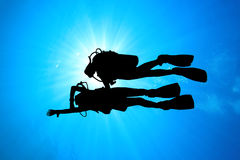 Scuba Divers. Instructor teaches an Open Water Student to navigate, silhouette against sunburst royalty free stock image
