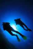 Scuba Divers. Silhouettes of Scuba Divers against sunburst stock photos