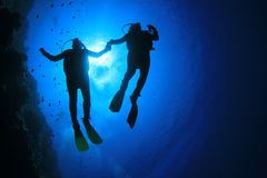 Scuba Divers. Silhouettes of Scuba Divers against sunburst royalty free stock image