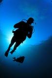 Scuba Divers. Two scuba divers silhouette against sun royalty free stock photos