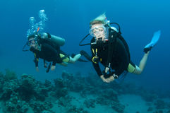Scuba divers. Friends scuba dive together in the ocean Stock Image