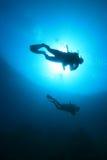 Scuba Divers. Two scuba divers silhouette against sun stock photos