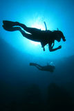 Scuba Divers. Two scuba divers silhouette against sun royalty free stock photography