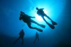 Scuba Divers. Group of scuba divers silhouette against sun stock photography