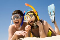 Scuba divers. Portrait of cheerful couple in aqualungs lying on sand and laughing Stock Photography
