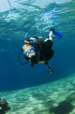 Scuba divers on coral reef Stock Images