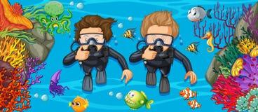 Scuba divers in the deep blue sea Stock Photos