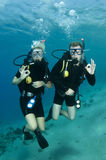 Scuba divers on a dive. Man and woman scuba divers gives OK sign royalty free stock photography