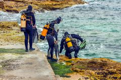 Malta Scuba divers enter the sea. Scuba Divers enter the Mediterranean off the coast of Malta at St. Elmos` Bay from the rocky coast Royalty Free Stock Photos
