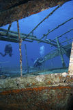 Scuba divers explore a shipwreck underwater Royalty Free Stock Photos