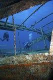 Scuba divers explore a shipwreck underwater. Underwater scene : Scuba divers are exploring a shipwreck in the mediterranean, Turkey royalty free stock photos