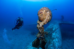SCUBA divers explore the wreck of an aircraft Royalty Free Stock Images