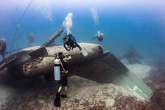 SCUBA divers explore the wreck of an aircraft stock image