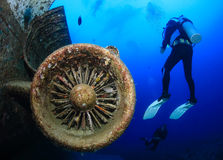 SCUBA divers explore the wreck of an aircraft Stock Photo