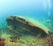 Scuba divers explore a wreck in the Indian Ocean. Antique oil tanker ship Conch lies on the sand in clear blue shallow waters off the west coast of Sri Lanka; a stock images